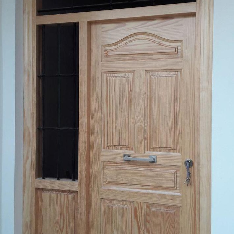 puerta de entrada de pino tea barnizada, con rejas de forja