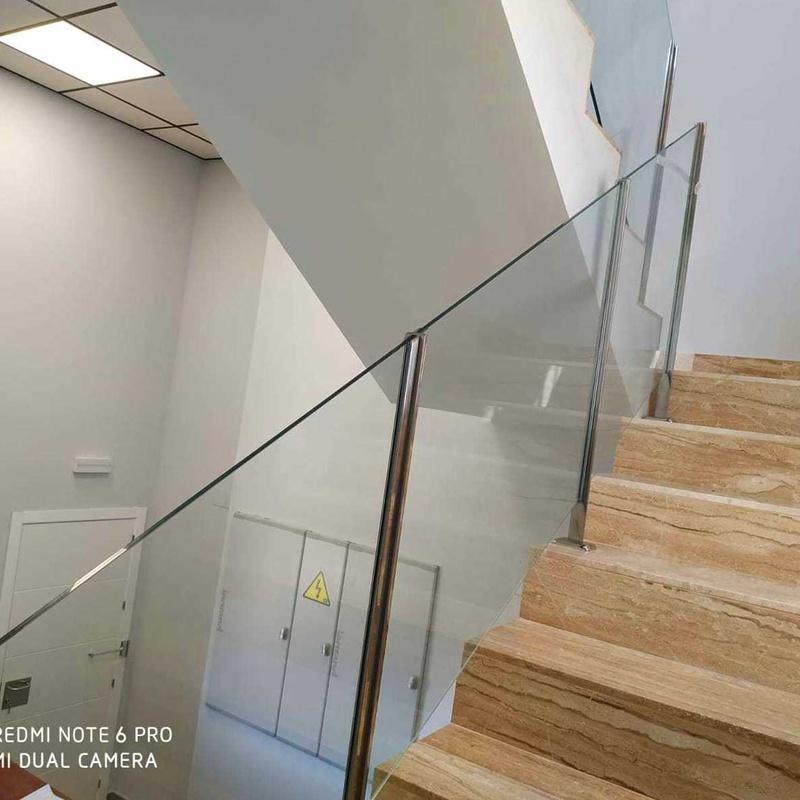 Barandilla de acero inoxidable con vidrio de seguridad sin pasamanos diseñada a medida y montada en oficinas de nave industrial.