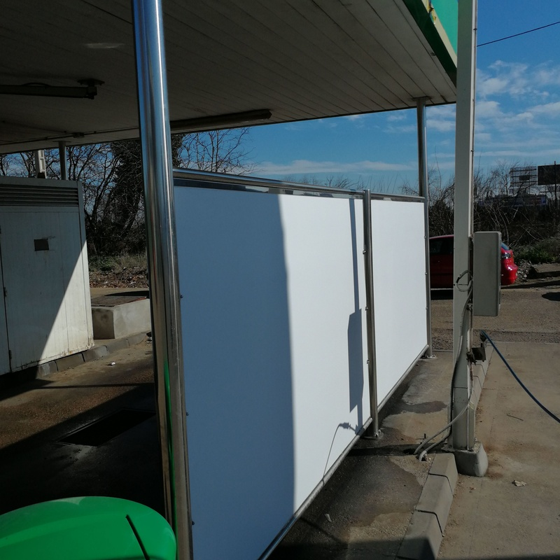 Pilares de acero inoxidable y mampara separatoria en lavadero a presión de estación de servicios.