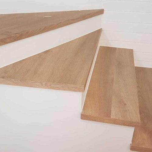 Peldaños prefabricados de laminado Ac5, y ajustados en obra por diferentes medidas.