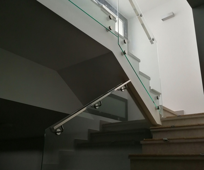 Barandilla de vidrio abotonado con pasamanos de acero inoxidable diseñada y fabricada a medida para chalet particular.