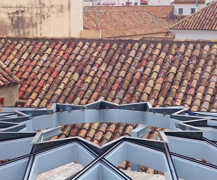Estructura de acero negro con forma de estrella formando una base totalmente plana para alojar un vidrio con la misma forma diseñado y fabricado a medida  para techo de patio andaluz de palacete