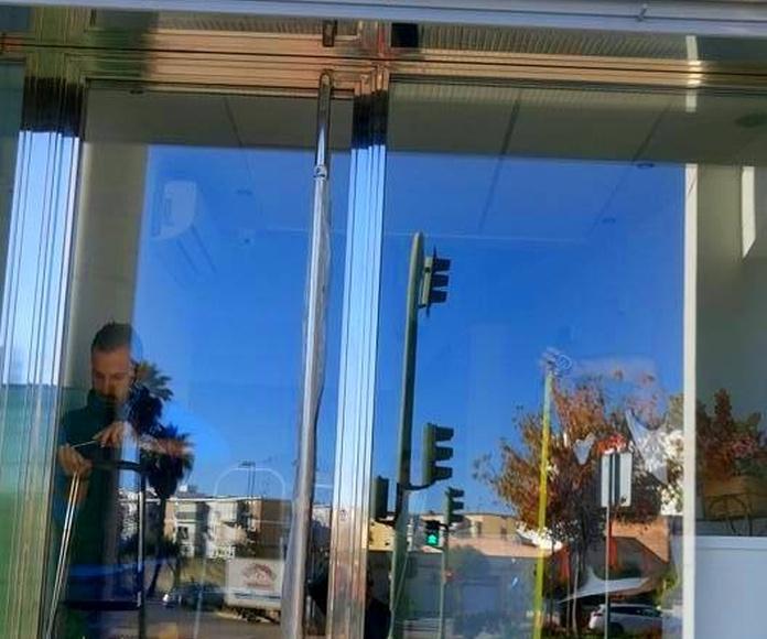 Cerramiento compuesto por puerta de acero inoxidable y escaparates diseñado y fabricado a medida para local comercial.