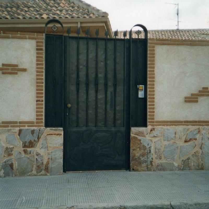 Puerta peatonal que imita al muro