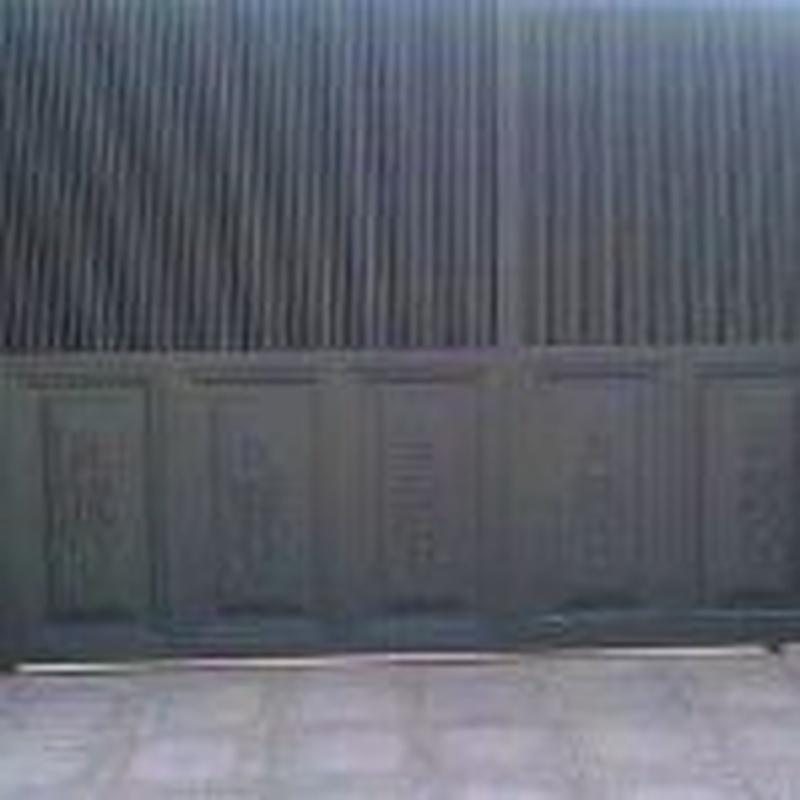 Puerta corredera con puerta de servicio incorporada.