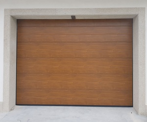 Puerta seccional residencial tableada en panel liso imitación madera clara (roble dorado).