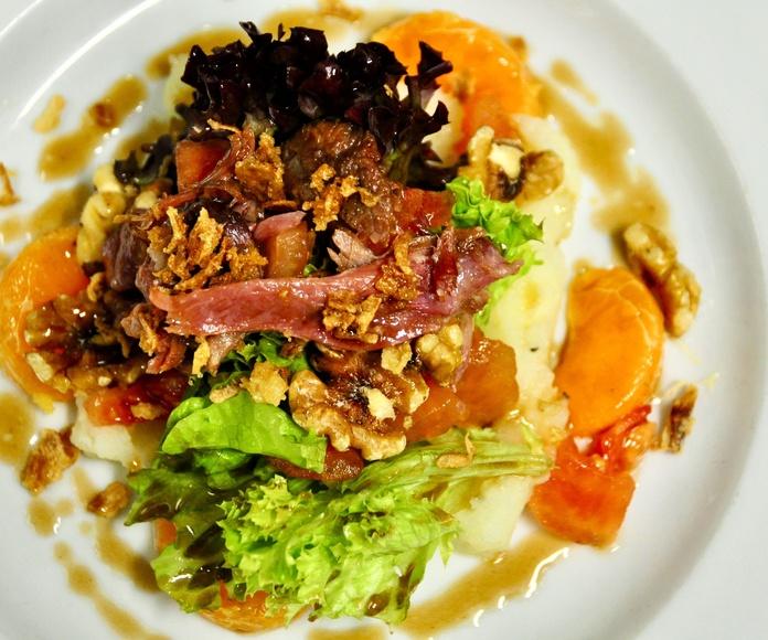 Ensalada templada de confit de pato y frutos secos.