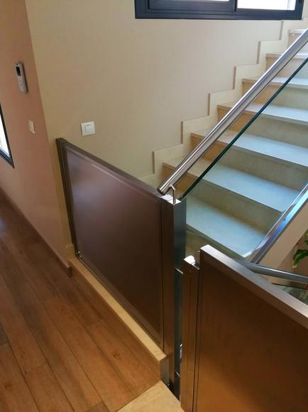 Puertas de acero inoxidable de barrera de protección infantil en escaleras, montadas en chalet particular.