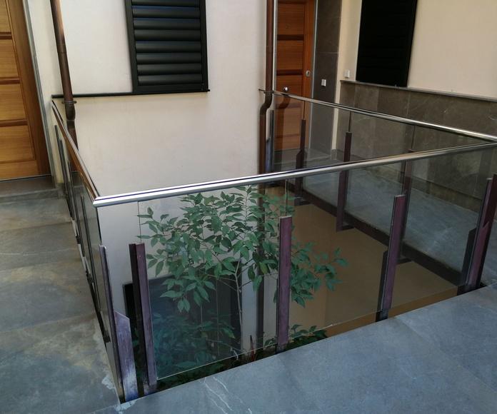 Pasamanos de acero inoxidable con alojamiento en vidrio para comunidad de vecinos.
