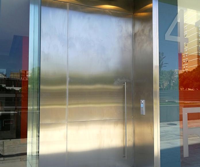 Puerta de acero inoxidable con diseño personalizado para edificio de comunidad de vecinos.
