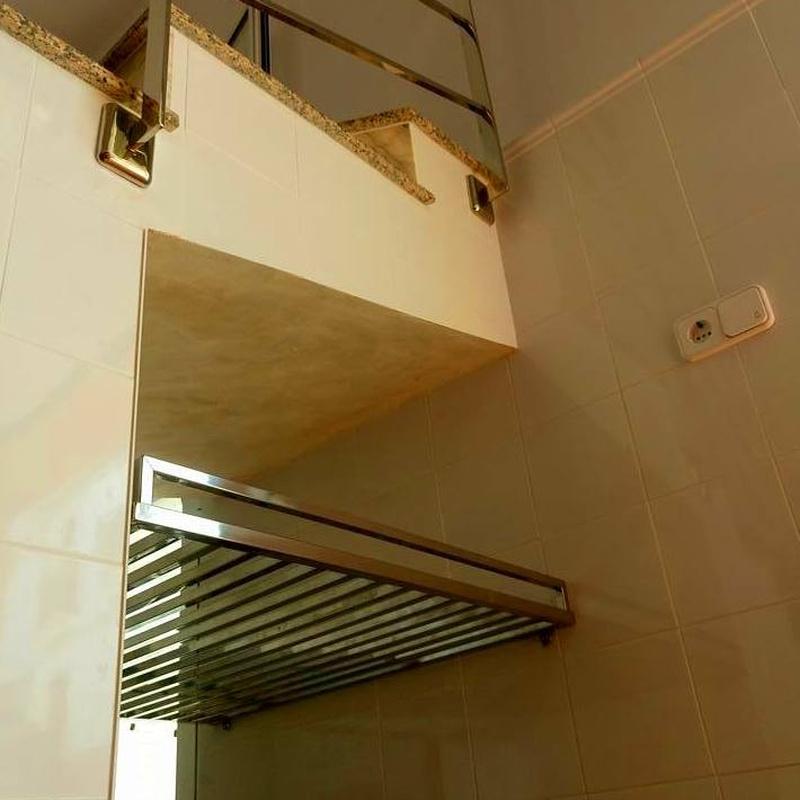 Estantería de acero inoxidable diseñada y fabricada a medida para hueco de escalera de garaje de vivienda particular.