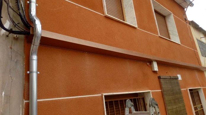 Trabajo de cubrir cables en fachada