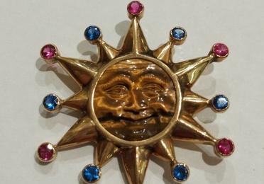 Colgante de sol en oro de 18k con ojo de tigre y vidrios. 1980.