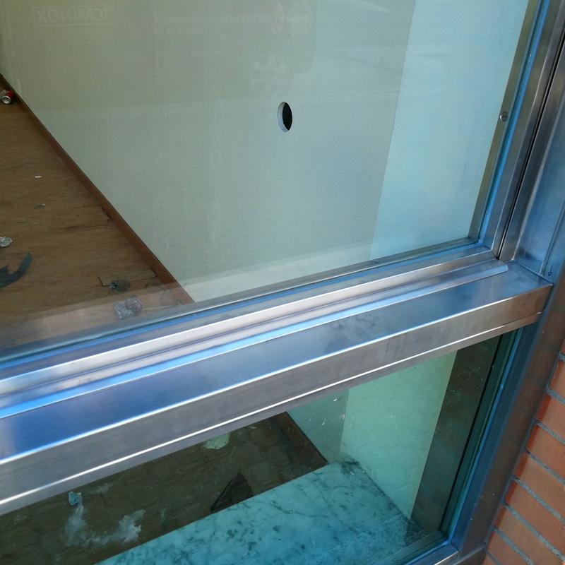 Ventana guillotina de acero inoxidable y vidrio montada para escaparate de local comercial.