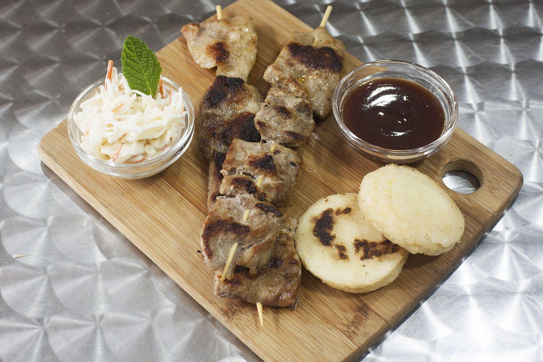 Pincho de cerdo con salsa BBQ, arepa y ensalada