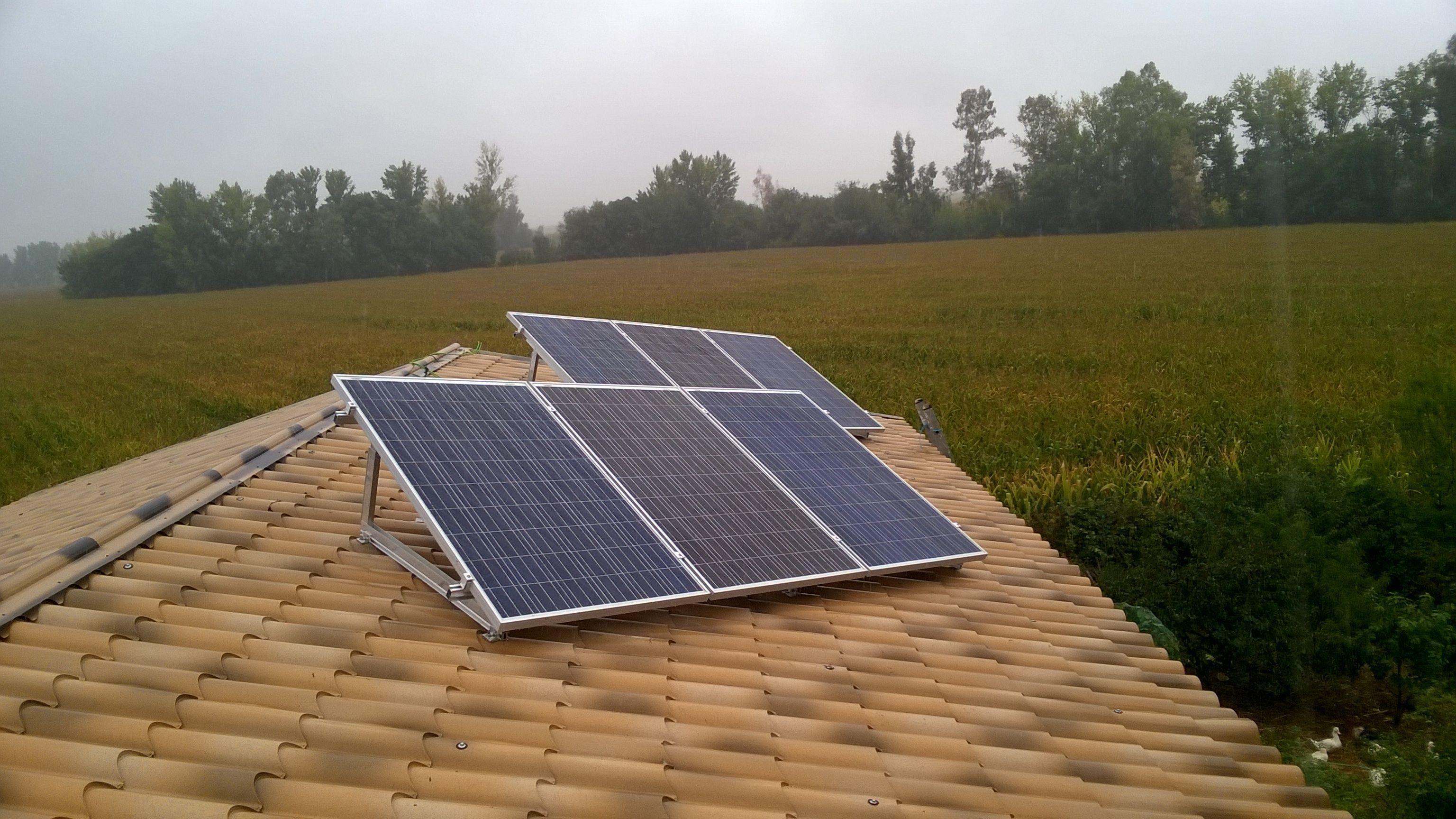 Módulos fotovoltaicos en soporte de aluminio en cubierta inclinada.