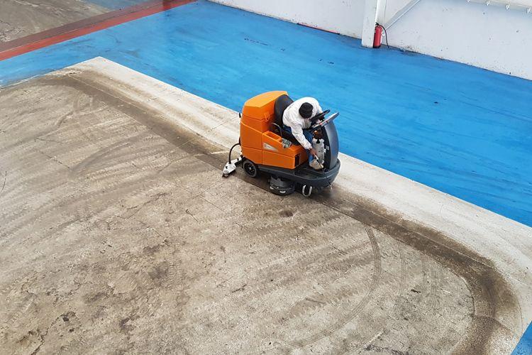 Limpieza de suelos de nave con fregadora grande
