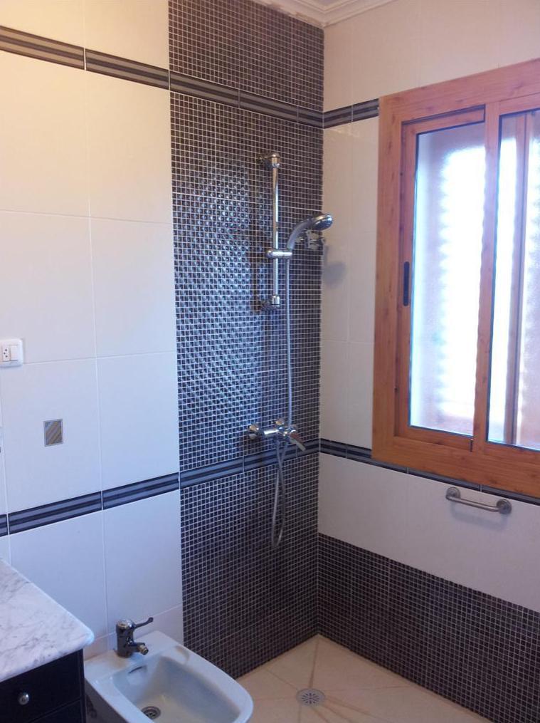 Modificación baño colocando, plato de ducha en mármol compact crema, y solamente cambiando azulejos frente grifería y las zonas bajas