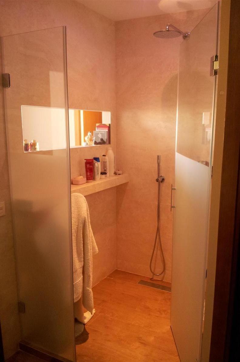 Zona ducha con soleria porcelanica imitación madera, aplacado porcelanico y griferia Grohe empotrada en pared con ducha tipo lluvia. Detalle de ventanal hacia dormitorio con vidrio laminar.