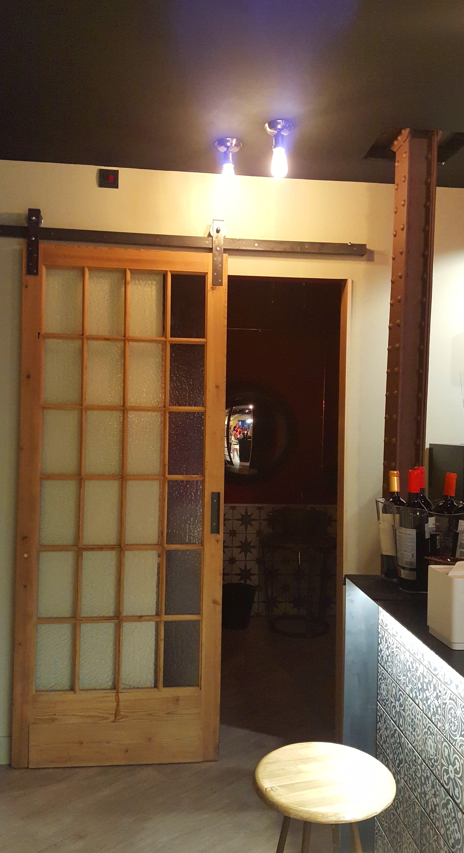 Carriil y rodamientos en hierro visto para puerta corredera de madera en Casco Viejo Bilbao