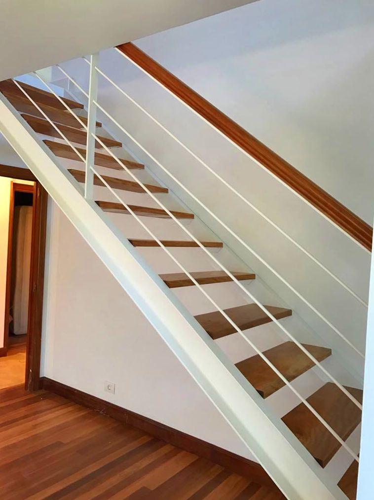 Escalera con viga de hierro vista y barandilla en color blanco en Plentzia