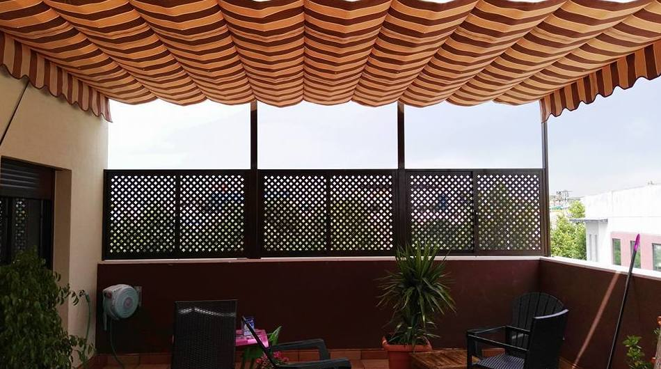 Ventanas de aluminio color marrón con rejillas para cerramientos de terrazas