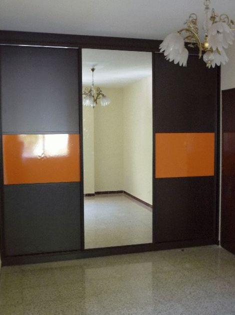 Armario empotrado de formica de color wengé y naranja con espejo enterizo