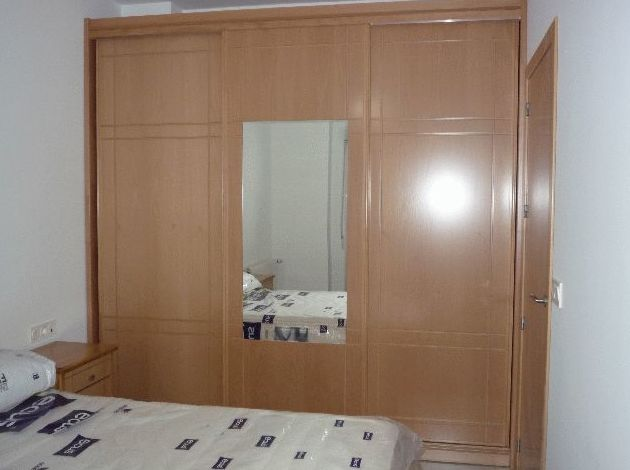 Armario empotrado con puertas en haya natural con puertas de correderas y espejo