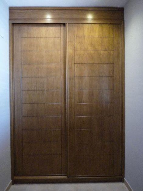 Armario empotrado barnizado en color nogal medio con puertas de corredera