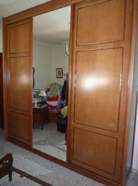 Armario empotrado barnizado en nogal claro con puertas de corredera y espejo enterizo