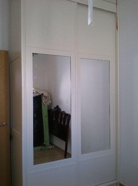 Armario empotrado lacado en blanco con puertas de corredera y espejos