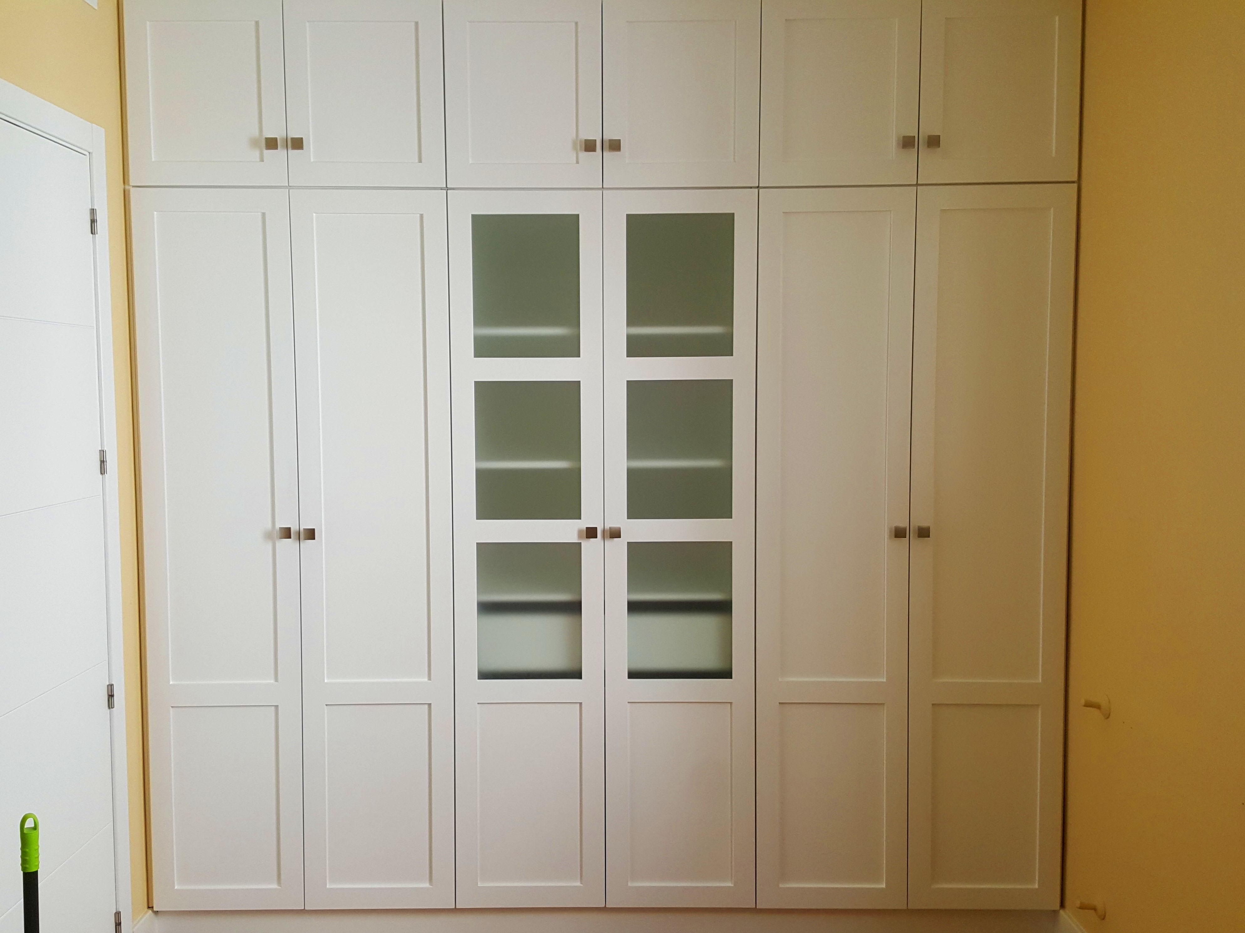 Armario empotrado lacado en blanco con puertas abatibles y cristal mate