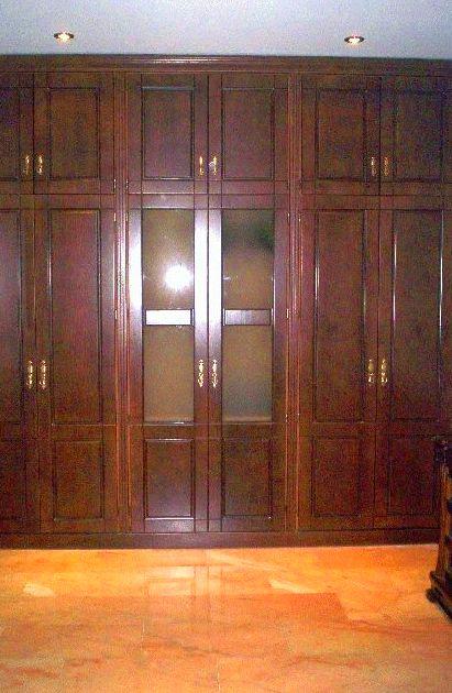 Armario empotrado barnizado en color nogal oscuro con puertas abatibles