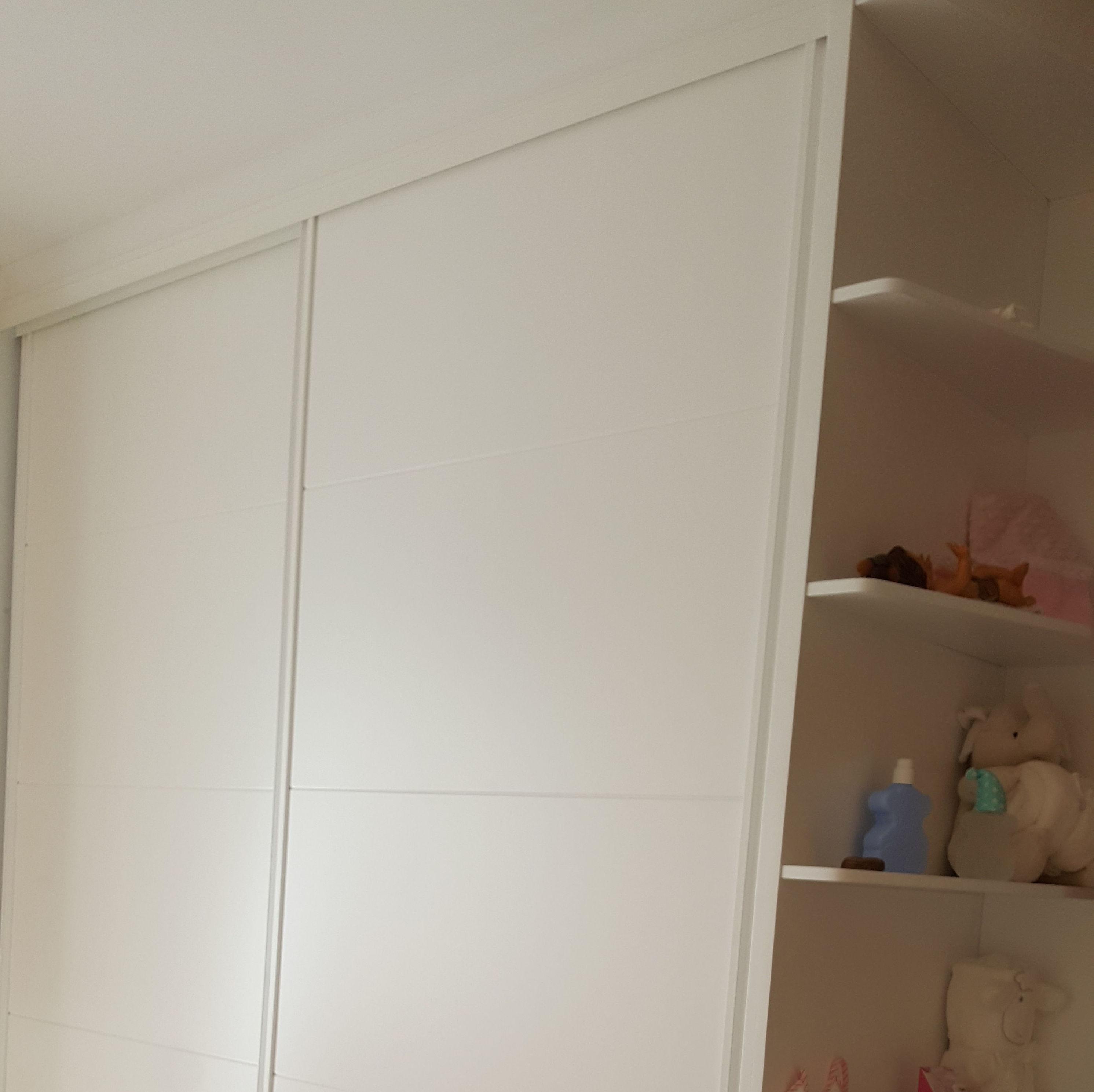 Armario empotrado lacado en blanco con puertas de corredera y terminal decorativo