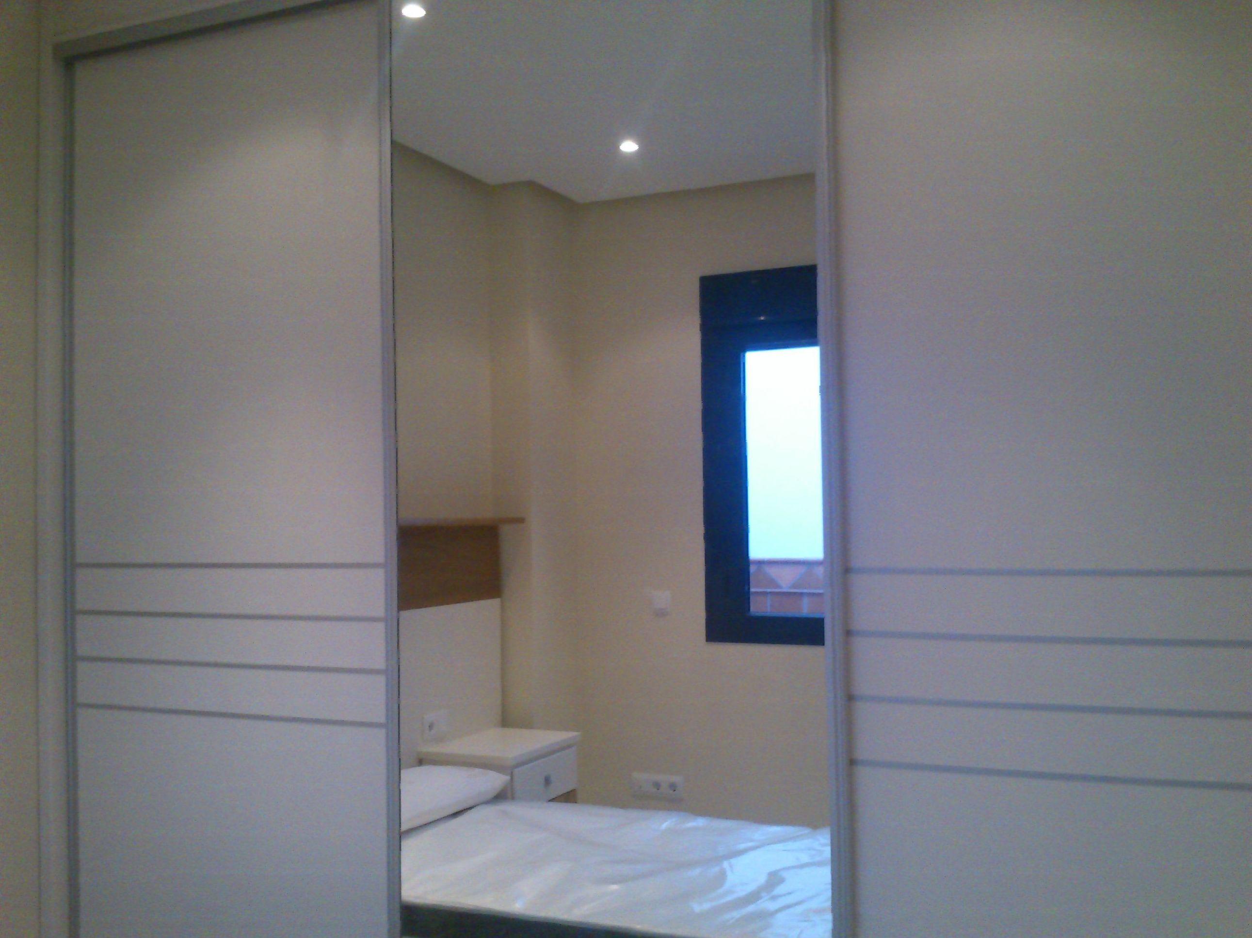Armario empotrado lacado en blanco con puertas de corredera y espejo enterizo