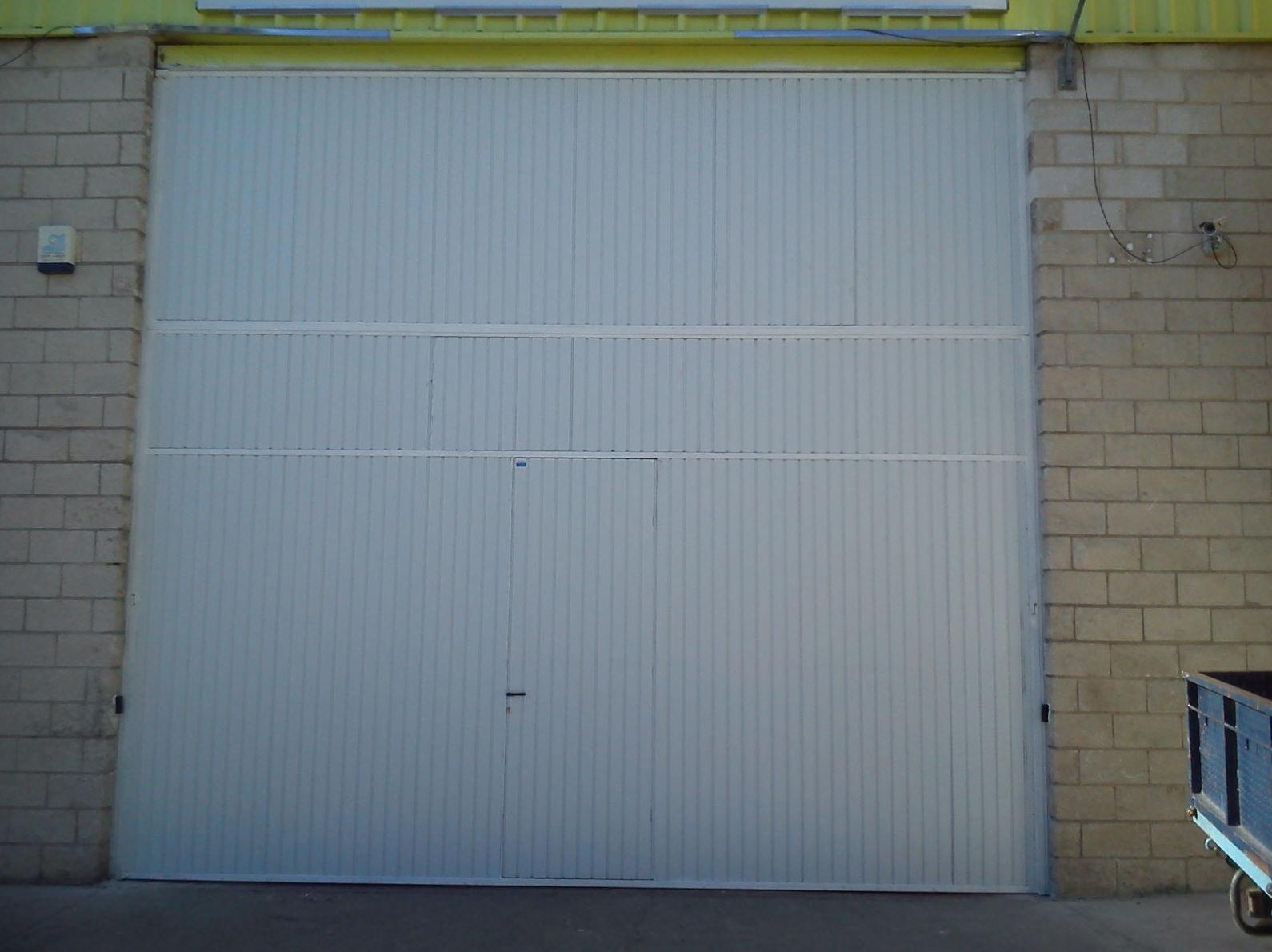 Puerta basculante industrial, con puerta de servicio integrada