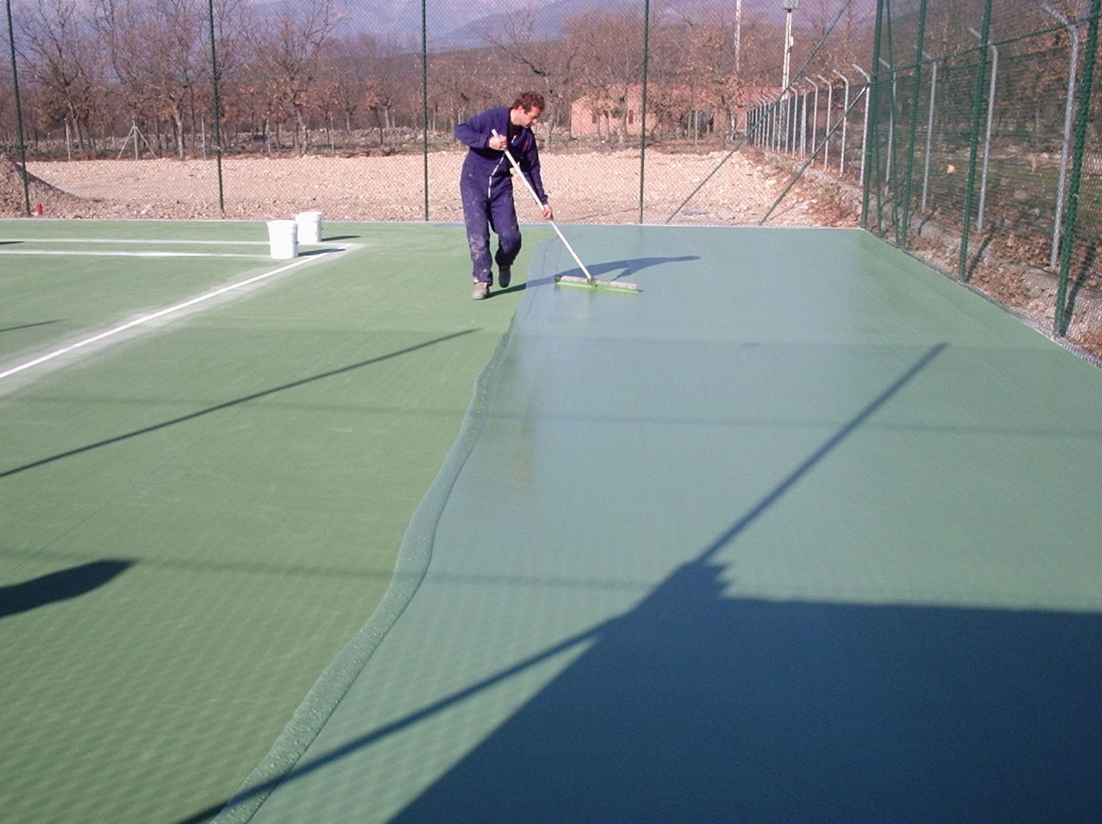 Aplicación resina sintética en pista tenis, capa intermedia