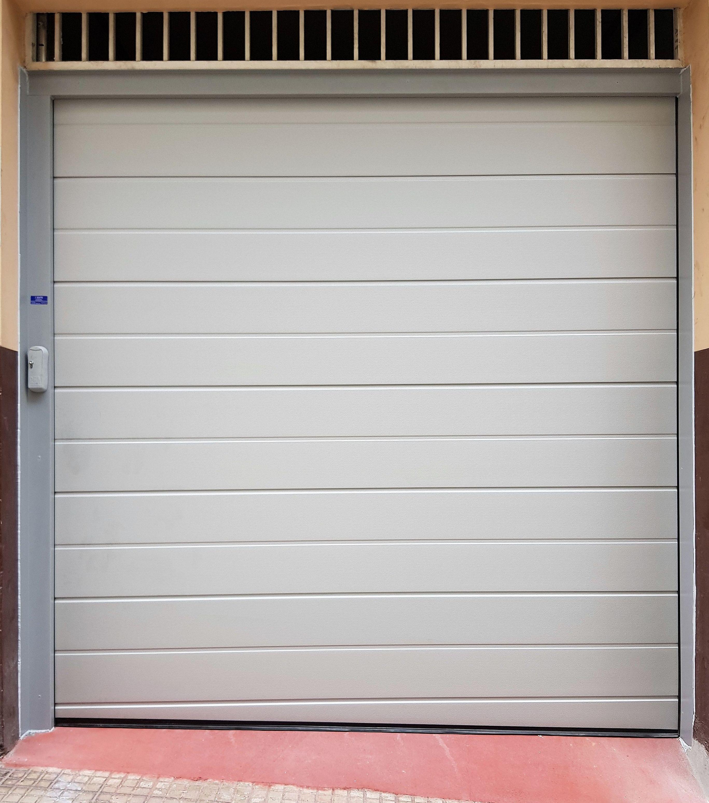 Puerta seccional tableada en color RAL 9006. Bajera cortada en inglete.