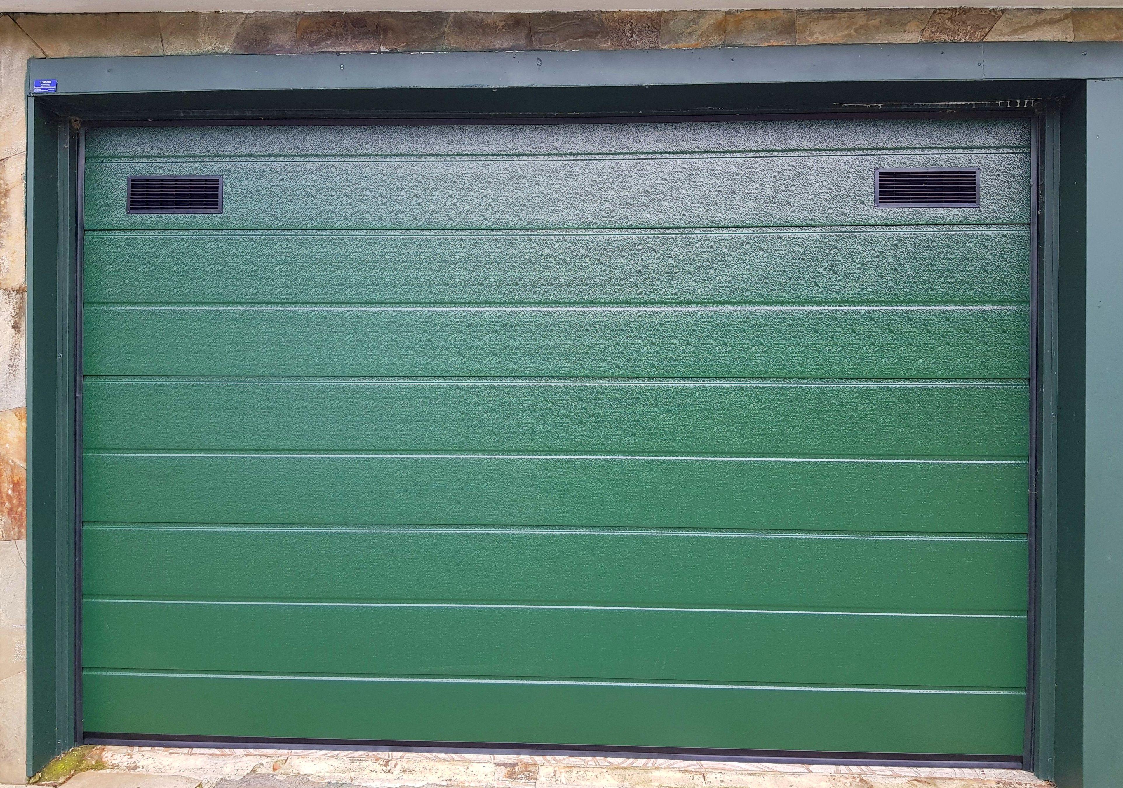 Puerta seccional residencial tableada con rejillas de ventilación en panel superior. RAL verde 6009.