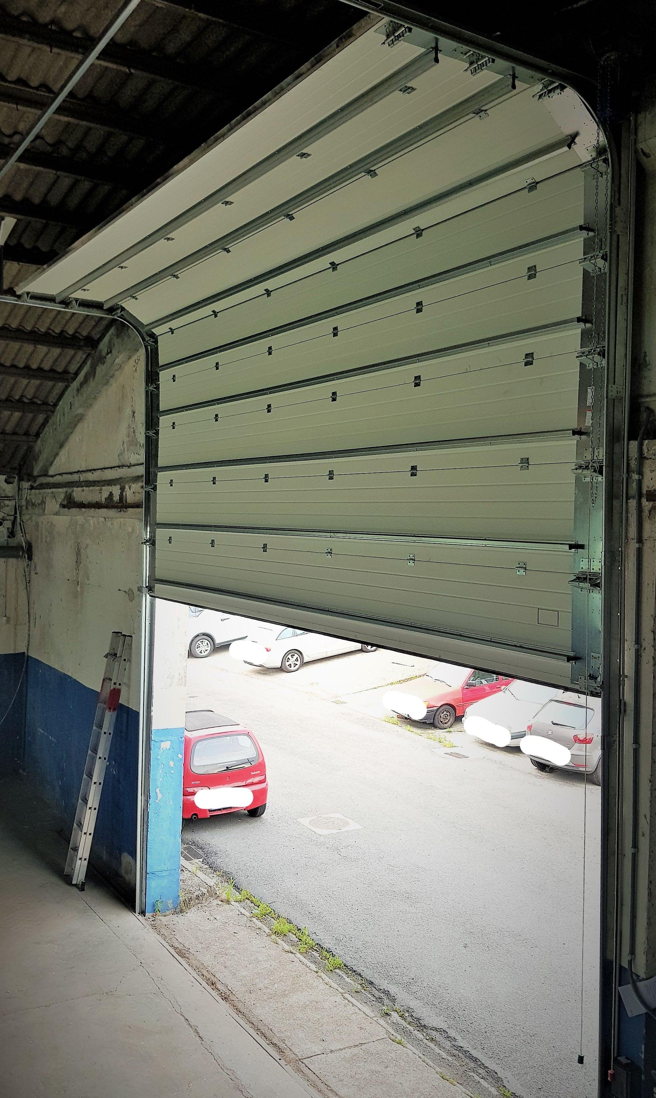Puerta seccional de gran formato con caballetes y portarrodillos dobles. Elevación en semiguillotina. Vista interior.