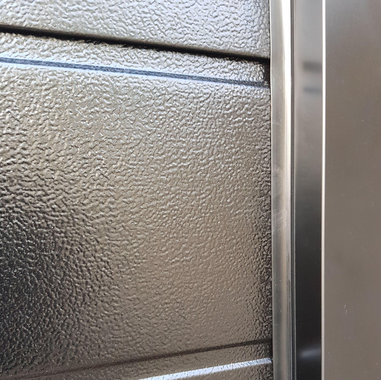 Puerta seccional residencial gofrado stuco en RAL 9005. Detalle de premarco y goma de cierre lateral.