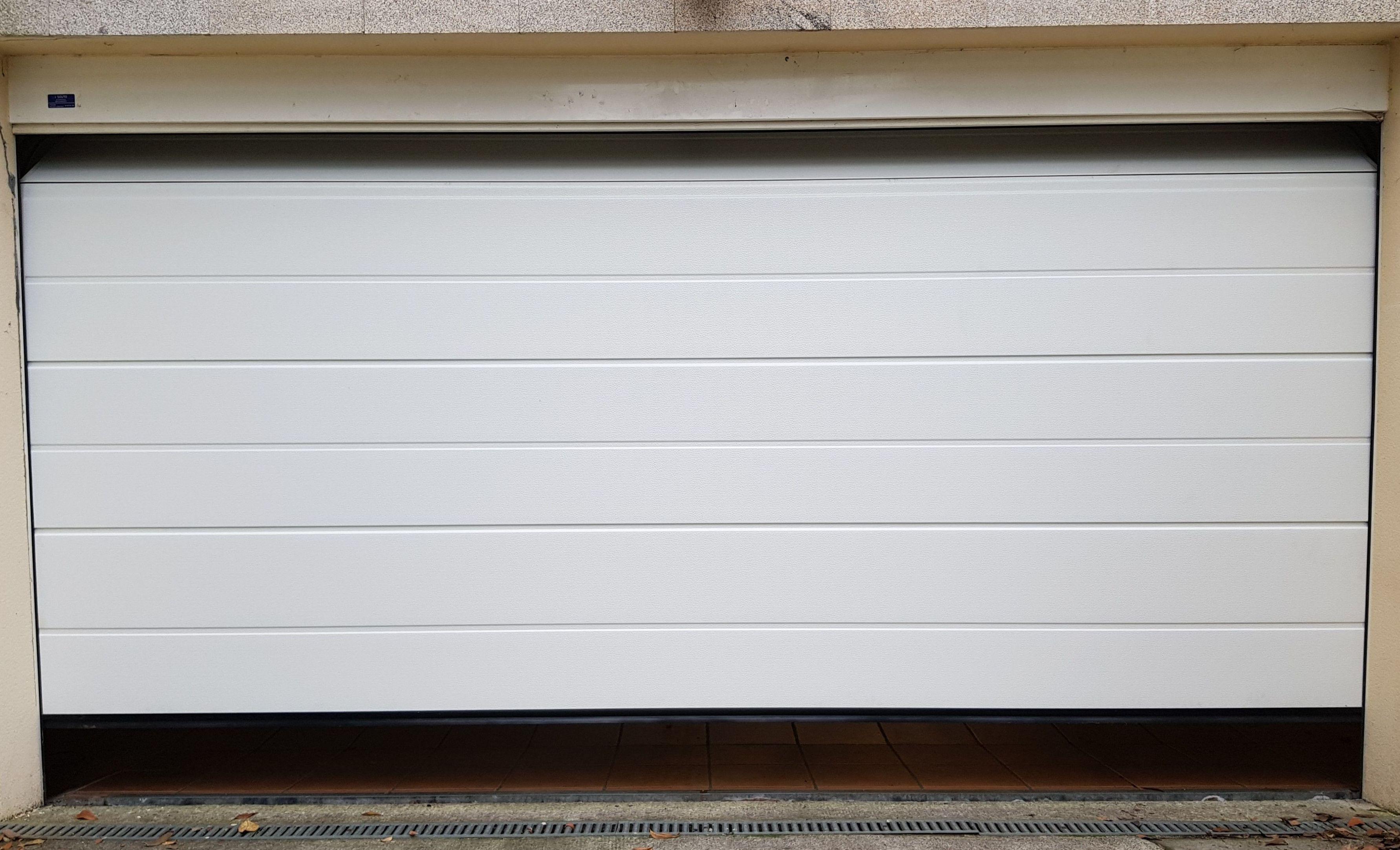 Puerta seccional residencial tableada gofrado estuco unicanal 9016.
