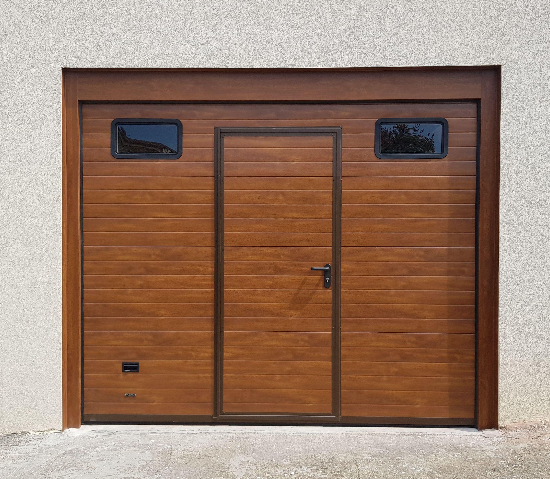 Puerta seccional en madera clara, con ventanas y peatón de apertura exterior. Remate de marco en imitación madera.