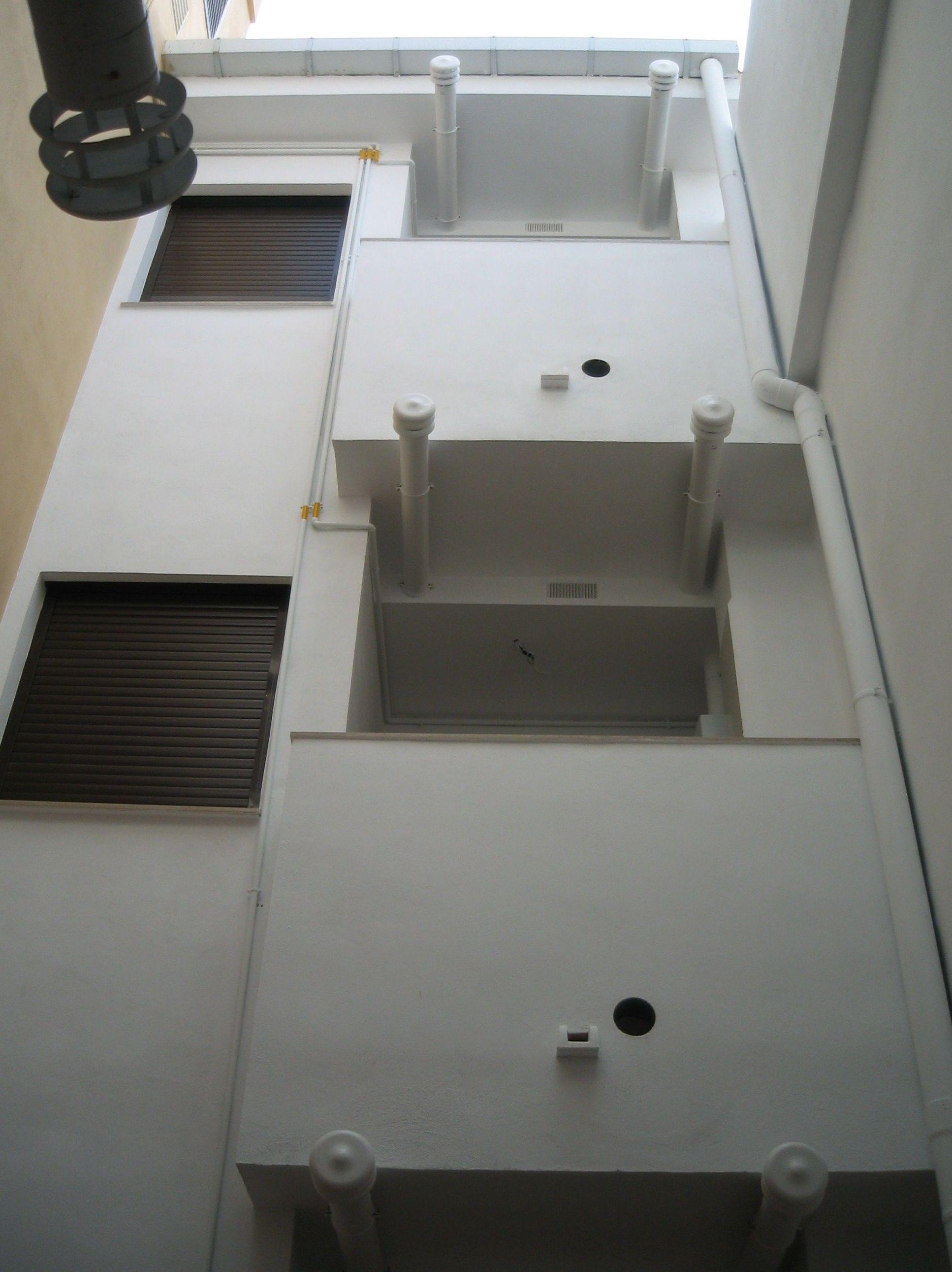 Patio de luces donde se puede ver la instalación de bajantes y la de extracción de humos en cocinas.