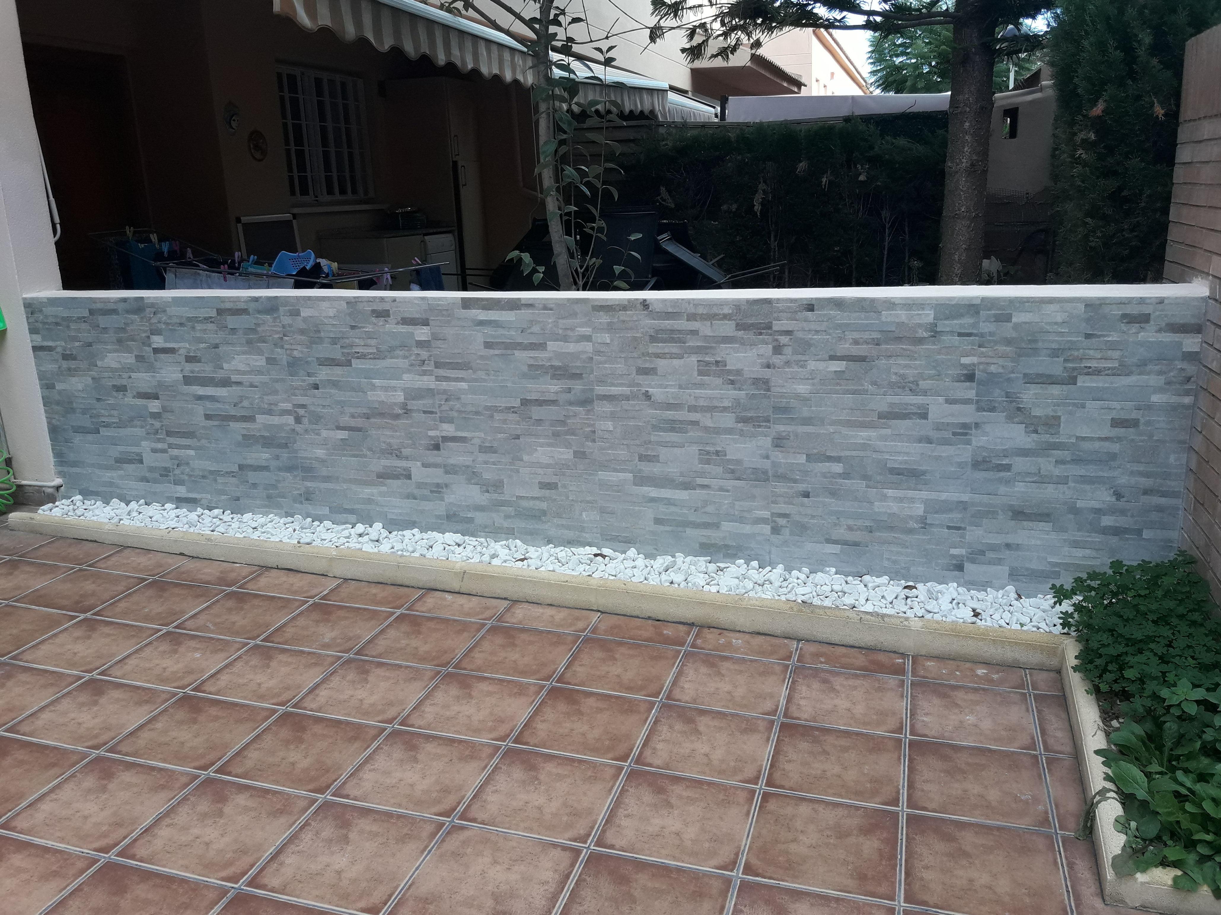 Muro medianera, chapado y jardinera con piedra decorativa.