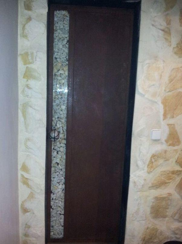 Puerta corredera de hierro con tirador de piedra. Piedras decorativas en parte interior.