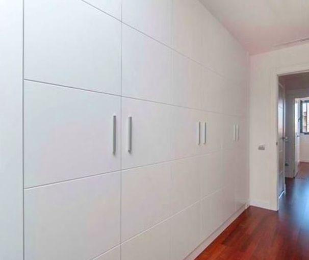 Un armario a medida de gran capacidad lacado en blanco