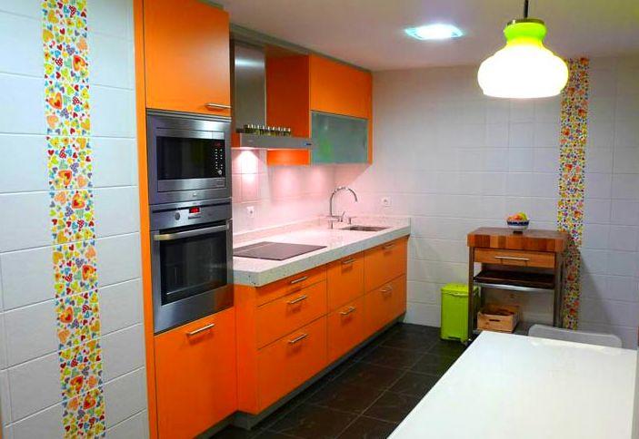 Cocina de diseño moderno color naranja y aluminio.
