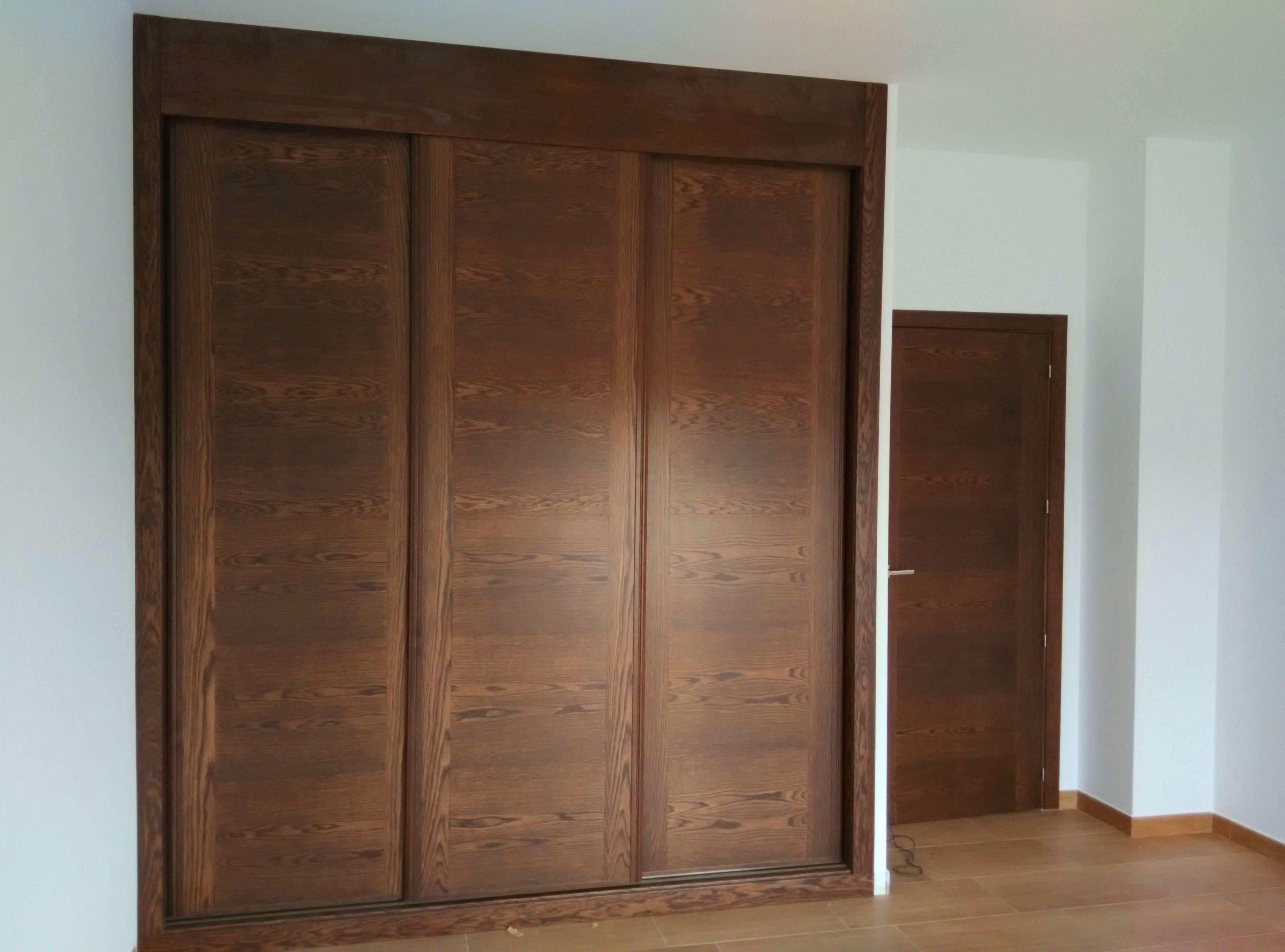 Frente de armario corredera con puertas de roble teñido en nogal.