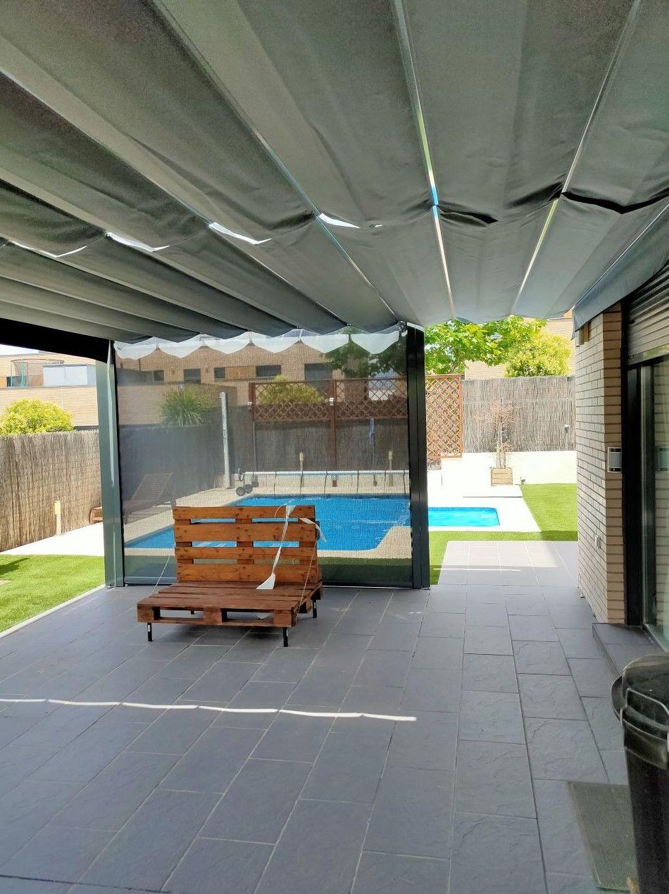 Pérgola 125X125 con toldo vertical con tejido microperforado para poder ver la piscina